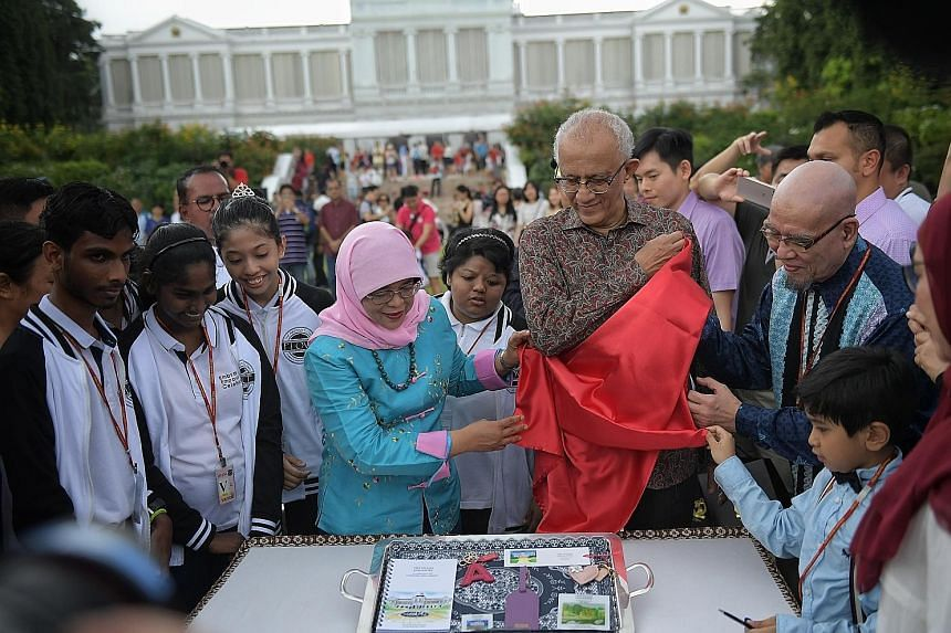President Halimah Yacob unveiling the President's Challenge memorabilia during the Istana's Open House yesterday, the second day of Chinese New Year. With her is her husband, Mr Mohamed Abdullah Alhabshee.