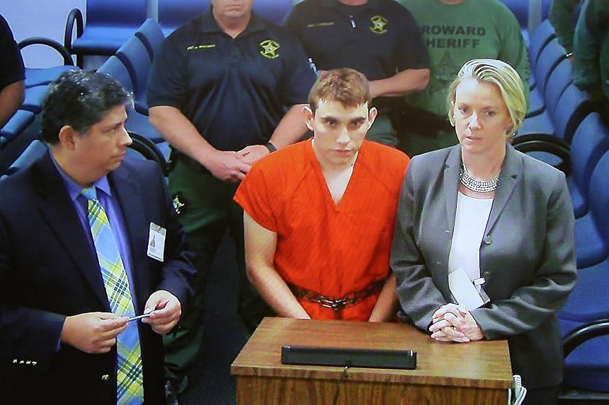 Above: Mourners grieving as they wait for a candlelight vigil to begin in Parkland on Thursday. Below: Suspect Nikolas Cruz (centre) at a Broward County court, where he was charged with 17 counts of premeditated murder. Initial reports point to a tro