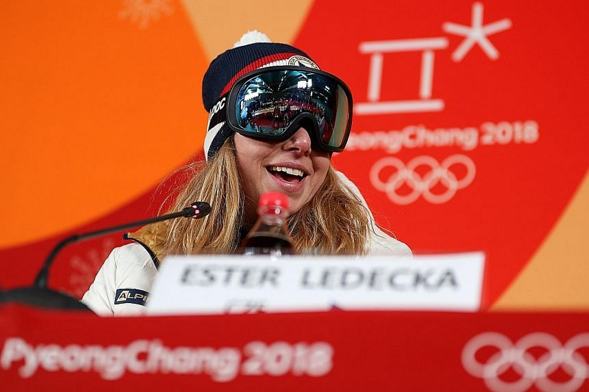 "A joyous Ester Ledecka wearing ski goggles at a news conference, as she was not as prepared as the others ""and I don't have no make-up"". She was ranked only 43rd in the World Cup super-G standings."