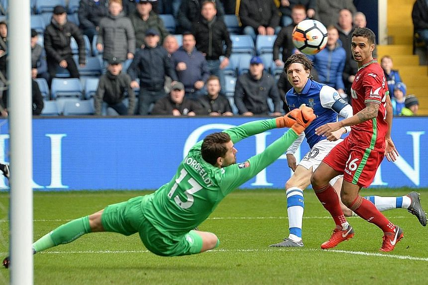 Swansea City's Kristoffer Nordfeldt saving a shot from Sheffield Wednesday's Adam Reach during yesterday's 0-0 draw in their FA Cup fifth-round clash at Hillsborough.