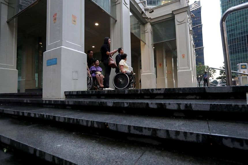 Wheelchair users Nongnuch Maytarjittipun (in purple) and Judy Wee outside Raffles Place MRT station. The station map shows nine exits from the underground passageways to buildings or the street level via stairs. But for wheelchair users, who can use