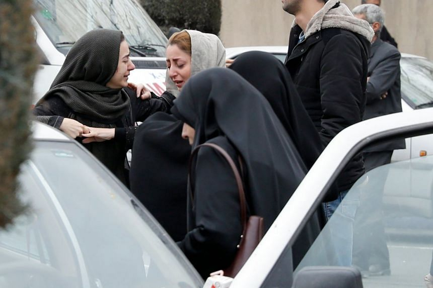 Relatives of passengers on board the Aseman Airlines flight that crashed grieving near the mosque at Mehrabad Airport in Teheran, on Feb 18, 2018.
