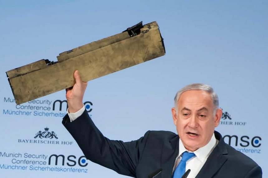 Israeli PM Benjamin Netanyahu holding up an object which allegedly came from an Iranian drone that was shot down in Israeli airspace, during a speech at the Munich Security Conference on Feb 18, 2018.