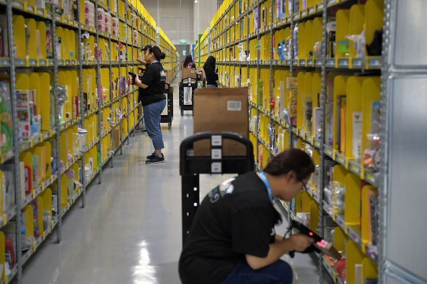 Staff from e-commerce platform Amazon preparing orders at their Prime Now facility, their largest global Prime Now facility located at the Mapletree Logistics Hub on Toh Guan Road East.
