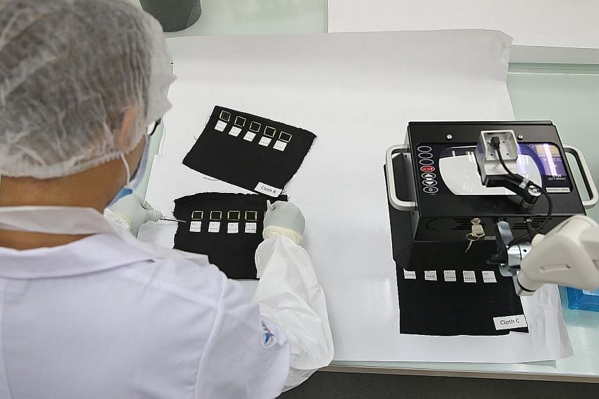 A lab officer examines a shirt as part of the training to look for traces of DNA left behind at crime scenes. A laboratory officer (left) examines different dilutions of blood on pieces of black cloth. While blood on dark cloth may not be visible to