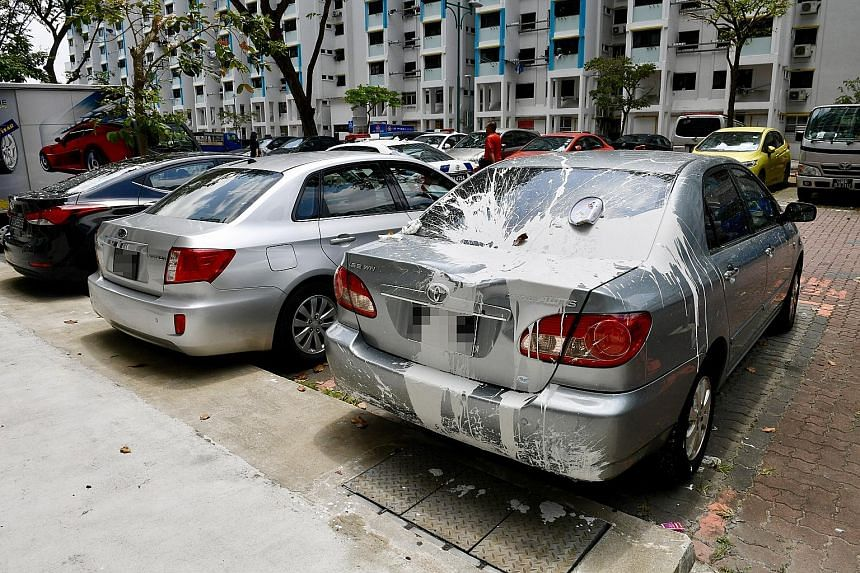 At least two cars in an HDB carpark were smeared with white paint yesterday after a man living on the fourth floor of a block threw household items and cans of paint down.