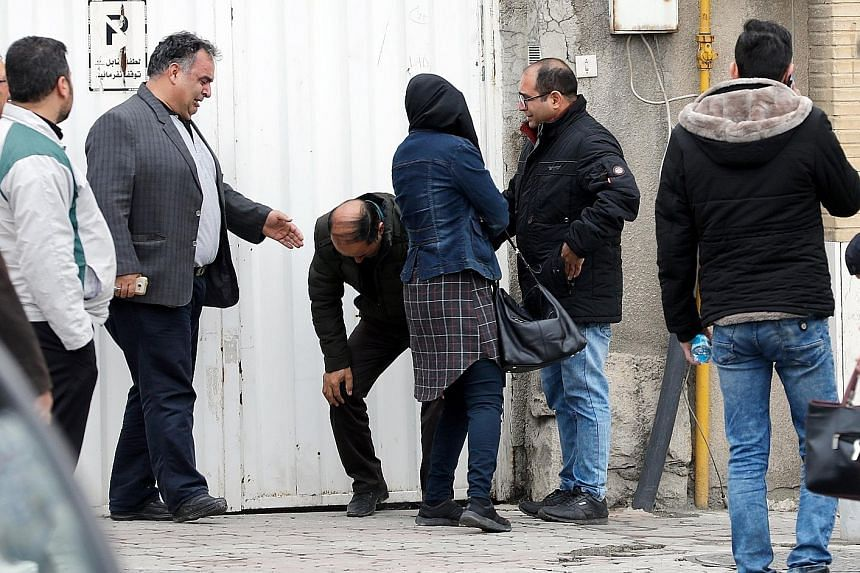 Grieving relatives of passengers on the Aseman Airlines plane at Teheran's Mehrabad airport yesterday. There were conflicting reports on the location of the crash site as emergency teams battled severe weather.