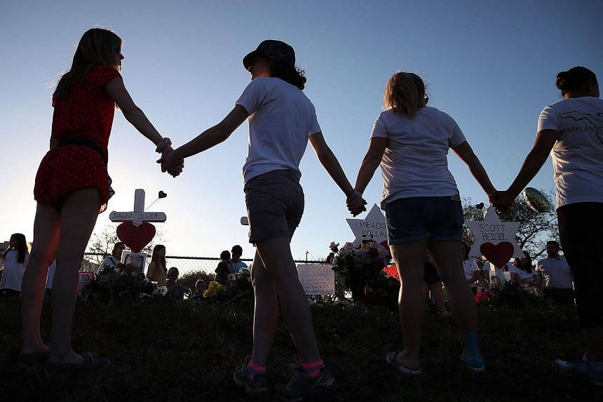 Students and family members hold hands around a makeshift memorial in front of Marjory Stoneman Douglas High School where 17 people were killed on Feb 14, 2018.