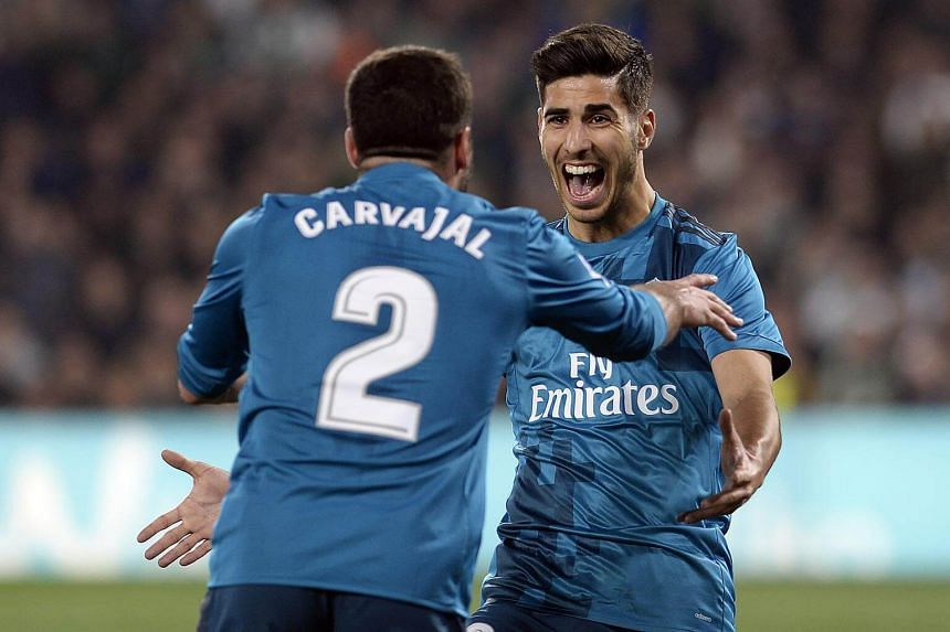 Real Madrid's Spanish midfielder Marco Asensio (right) celebrates a goal with Real Madrid's Spanish defender Dani Carvajal at the Benito Villamarin stadium in Sevilla on Feb 18, 2018.