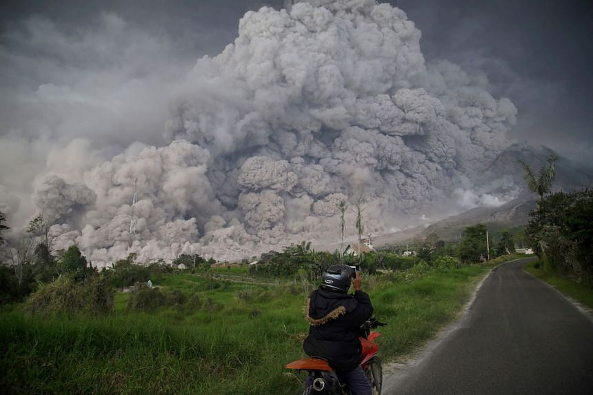 Mount Sinabung spewing out a massive cloud of smoke and ash after a pick-up in volcanic activity, on Feb 19, 2018.