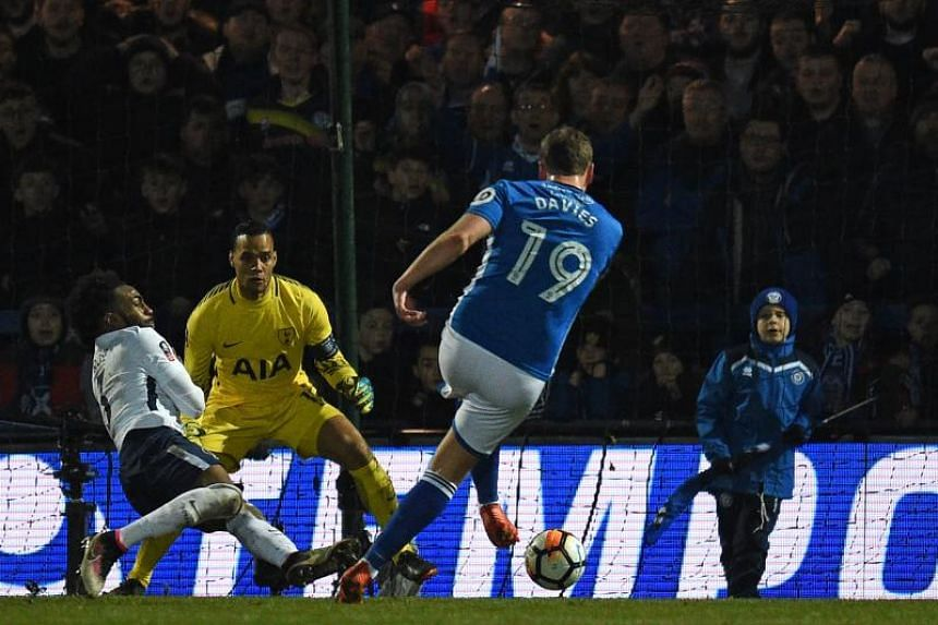 Rochdale's English striker Steven Davies (centre) shoots to score their late second goal during the English FA Cup fifth round football match between Rochdale and Tottenham Hotspur at the Crown Oil Arena in Rochdale, north west England on Feb 18, 201