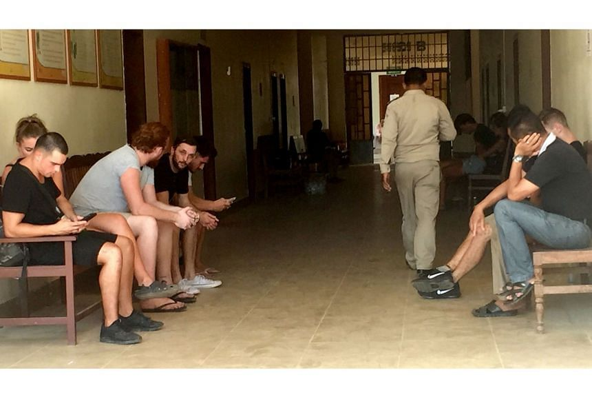 """A group of foreigners who were arrested for allegedly """"singing and dancing pornographically"""" sit outside a courtroom in Siem Reap on Jan 27, 2018."""