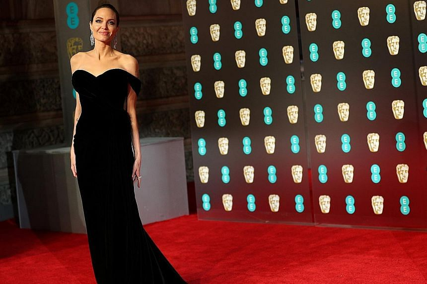 Stars making a statement in black include (clockwise from top left) Jennifer Lawrence, Lupita Nyong'o and Angelina Jolie. Catherine, the Duchess of Cambridge (with husband Prince William), however, chose to wear a dark green dress. (From far left) Di