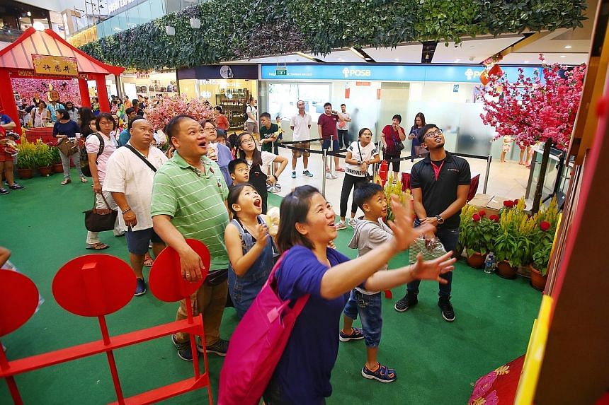 Mrs Cindy Goh spinning the Wheel of Fortune yesterday at Seletar Mall's Fortune Garden as her family cheered her on. Seletar Mall invited about 50 beneficiaries of The Straits Times School Pocket Money Fund (STSPMF) and their family members to an aft