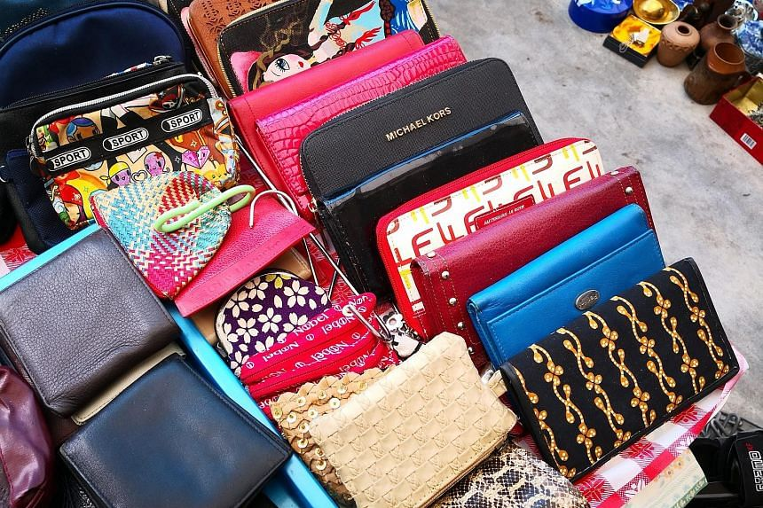 Some of the items karung guni collectors have picked up include spotless wallets from brands such as Michael Kors. Movers from waste disposal firm Junk To Clear removing an underused fitness machine from an apartment.