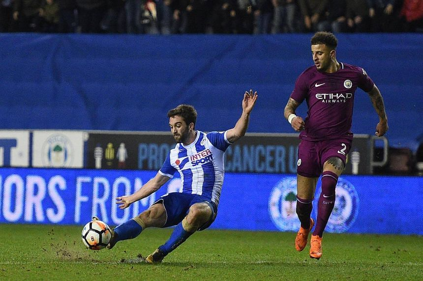 Wigan Athletic's English-born Northern Irish striker WillGrigg (left) scores his team's first goal during the English FA Cup fifth round football match against Manchester City at the DW Stadium in Wigan, northwest England, on Feb 19, 2018.