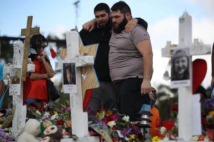 Max Bromberg hugs his brother Samuel, both of whom graduated from Marjory Stoneman Douglas High School, as they visit a makeshift memorial setup in front of the school.