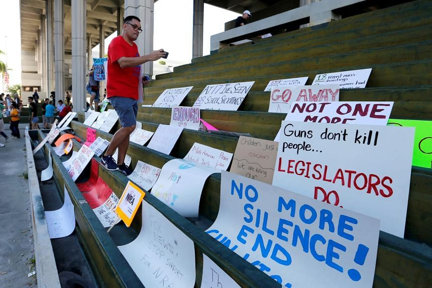 A school teacher from Florida, photographs signs during the March for Action on Gun Violence in Broward County at the US Courthouse in Fort Lauderdale, on Feb 17, 2018.