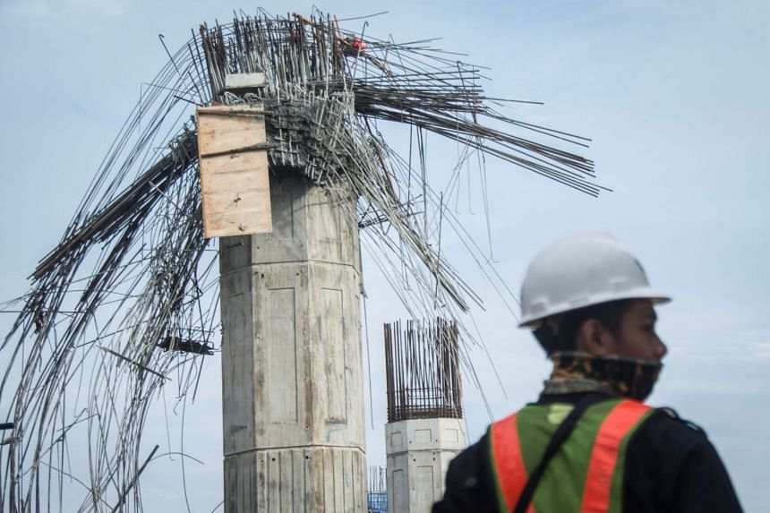 A worker standing near a collapsed girder pole on the construction site of the Bekasi-Cawang toll overpass in Jakarta on Feb 20, 2018.