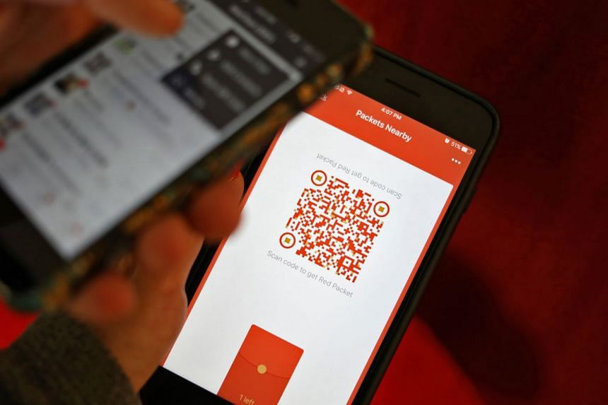 A user scanning a QR code to retrieve a digital red envelope, or hongbao, on the WeChat app during the Chinese New Year period in Beijing.