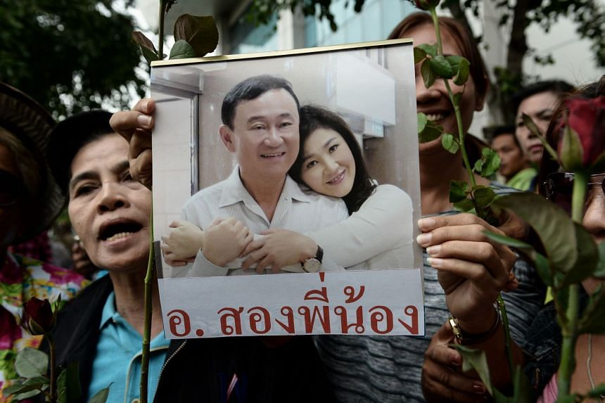Supporters holding a picture of Thaksin Shinawatra and his sister Yingluck in Bangkok on Aug 5, 2017. The two former Thai PMs were spotted in Singapore on Feb 20, 2018.