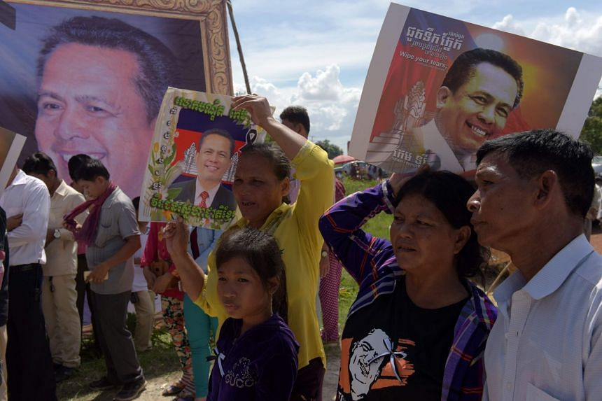 Cambodians hold images of prominent Cambodian critic Kem Ley on the first anniversary of his murder at his mother's home in Takeo province on July 9, 2017.