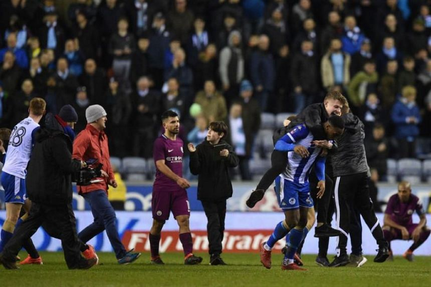 Manchester City's striker Sergio Aguero (centre) walks as supporters invade the pitch after the English FA Cup fifth round football match between Wigan Athletic and Manchester City.