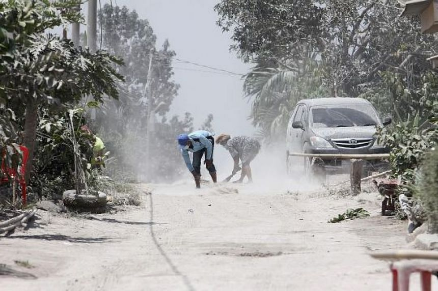 Volcanic ash being cleared from the street in Karo, North Sumatra, yesterday after Mount Sinabung spewed thick ash and smoke across the area the day before. The heightened activity covered hundreds of houses outside the 7km danger zone in volcanic as