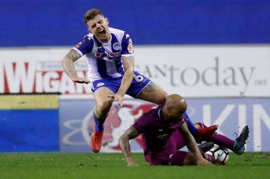 Manchester City's Fabian Delph leaving his studs up as he challenges Wigan's Max Power for a loose ball. Referee Anthony Taylor deemed it worthy of a red card, leaving the Premier League leaders to play out the entire second half with 10 men.