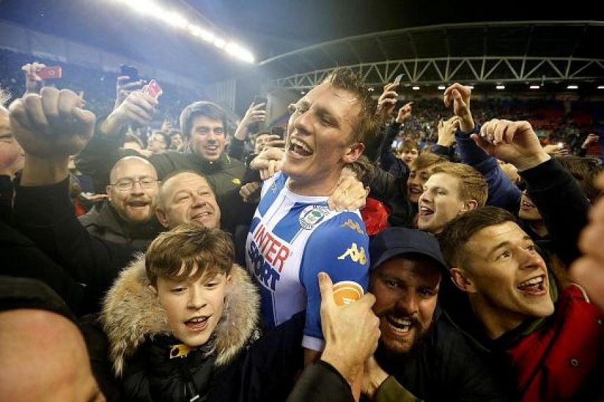 Wigan's Dan Burn soaking up the post-match jubilation with fans who thronged the pitch after the final whistle. The League One side may face punishment after some fans got into a scuffle with City striker Sergio Aguero amid the celebrations.