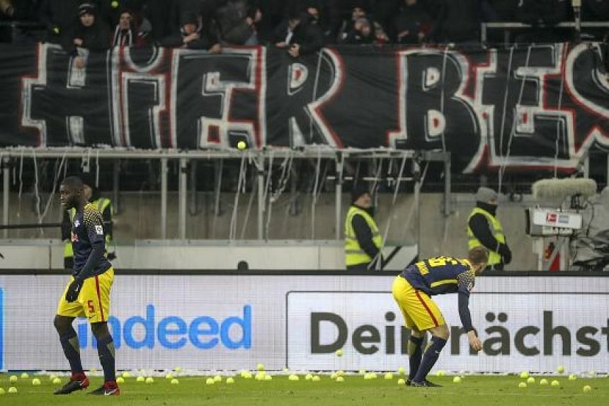 Angered by the decision to play football on Monday nights, fans threw hundreds of tennis balls onto the pitch, delaying Eintracht Frankfurt's 2-1 victory against RB Leipzig on Monday.