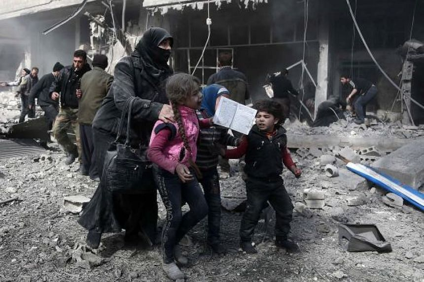 Civilians running for cover from the bombing in the rebel-held town of Hammuriyeh, Eastern Ghouta, on Monday. A total of 127 civilians, including 39 children, were killed in Monday's bombardment, making it the bloodiest day for the Syrian enclave in