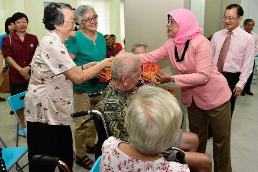 President Halimah Yacob giving mandarin oranges to Madam Boh Cheak Wah, 90, at the Serangoon Moral Family Services Centre yesterday. During her visit to the centre in Serangoon Avenue 2, Madam Halimah also launched a food donation drive where food it