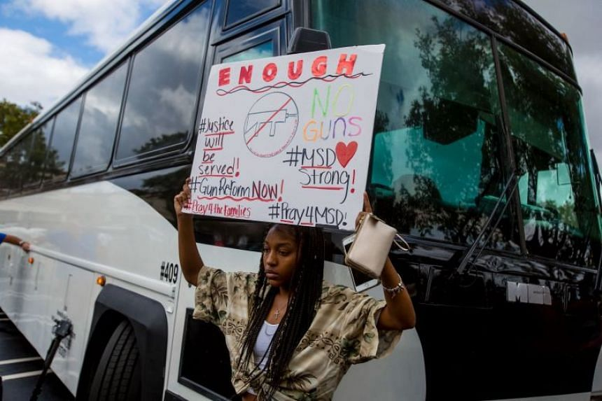 Tyra Hemans from Marjory Stoneman Douglas High School, where 17 people were killed in a mass shooting last week, holding up a sign before boarding the bus to Tallahassee, the state capital, to call for a ban on assault rifles, on Feb 20, 2018.