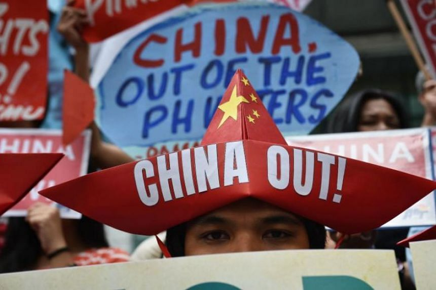 Activists holding placards protesting in front of the Chinese consulate in Manila on Feb 10, 2018.