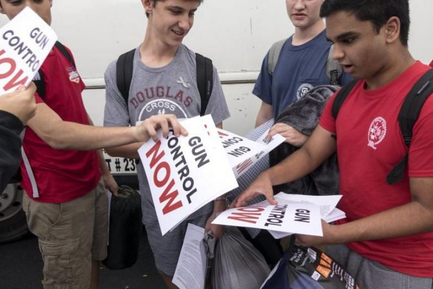 Students from Marjory Stoneman Douglas High School hold signs while waiting to board buses in Parkland, Florida, on Feb 20, 2018.
