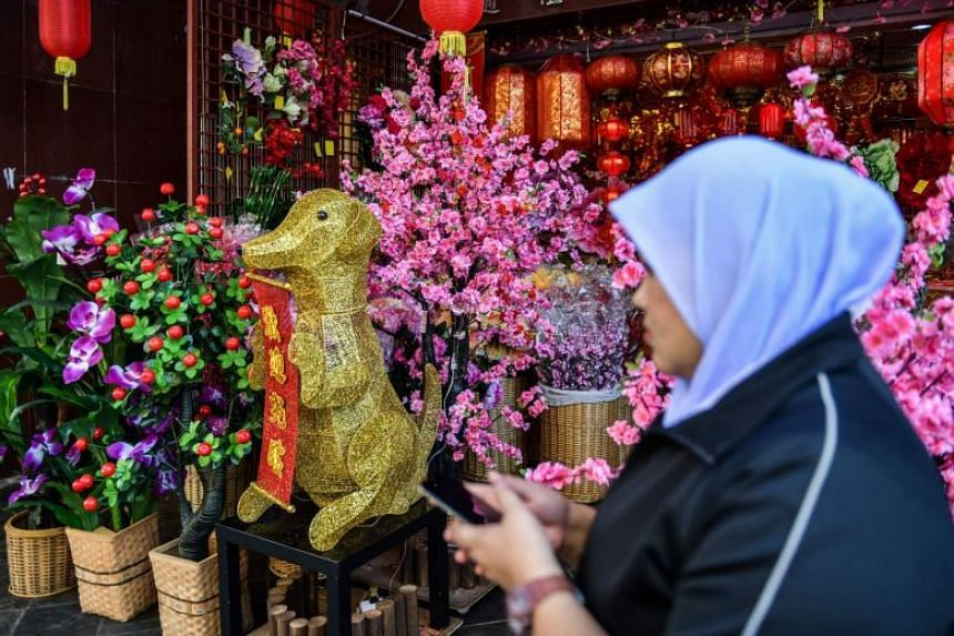 A woman walks past a golden canine statue ahead of the Chinese New Year celebrations in Kuala Lumpur's Chinatown, on Jan 26, 2018.