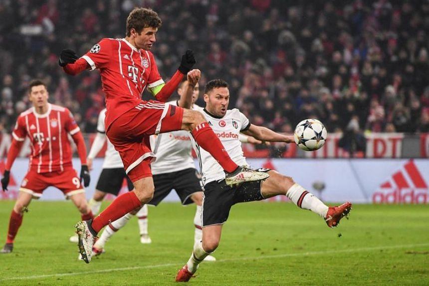 Bayern Munich's midfielder Thomas Mueller scores a second goal next to Besiktas' Serbian defender Dusko Tosic, on Feb 20, 2018.
