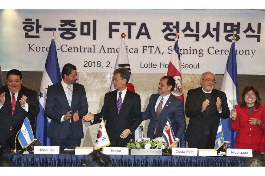 Trade officials of South Korea and five Central American nations congratulate each other after signing a free trade agreement in Seoul on Feb 21, 2018.