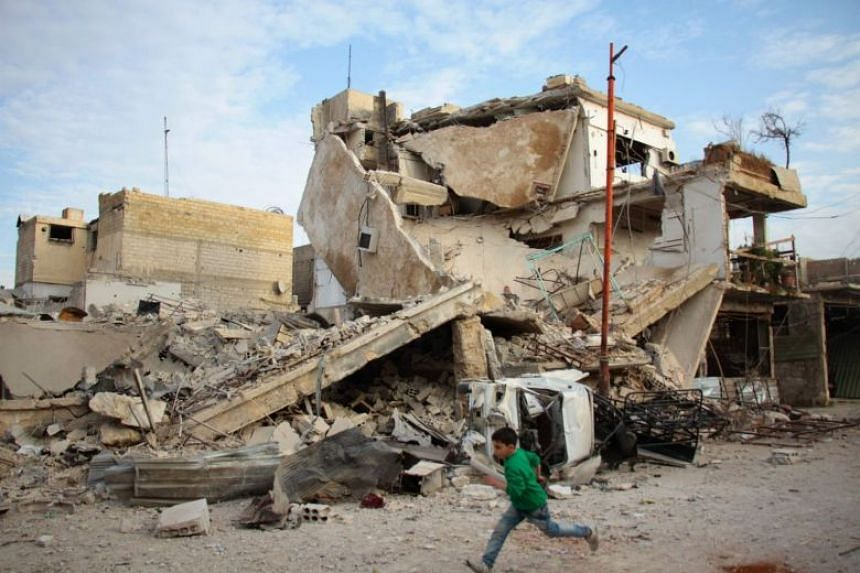 A Syrian boy runs past a destroyed building during air strikes by regime forces in Douma, Eastern Ghouta, Damascus, on Feb 20, 2018.