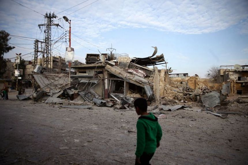 A child walks near damaged buildings in the besieged town of Douma, Eastern Ghouta, Damascus, Syria, on Feb 20, 2018.