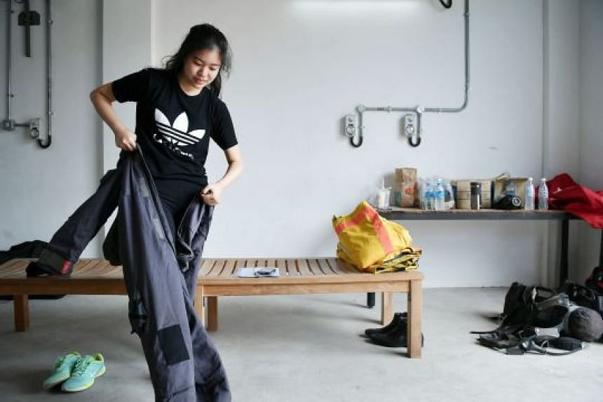Straits Times reporter Cheryl Tee puts on a chemical agent suit (above) and a light decontamination suit during her visit to the Home Team Tactical Centre earlier this month. During training and operations, marine firefighters wear equipment weighing
