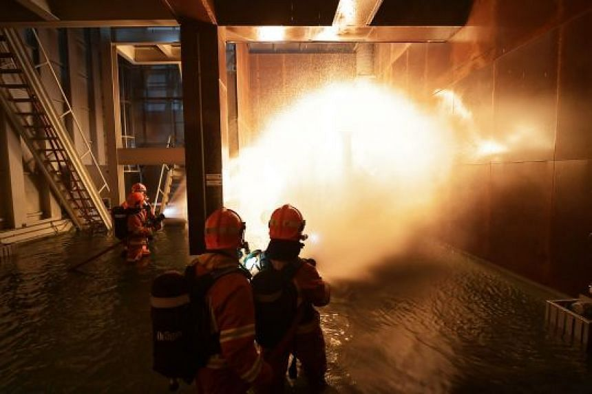 """SCDF Marine Command personnel simulate putting out an engine block fire on board the Orca. Such training """"gives our firefighters a very realistic environment to practise in"""", said West Coast Marine Fire Station commander Neo Jia Qi."""