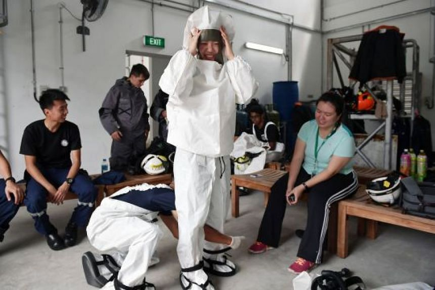 Straits Times reporter Cheryl Tee puts on a chemical agent suit and a light decontamination suit (above) during her visit to the Home Team Tactical Centre earlier this month. During training and operations, marine firefighters wear equipment weighing