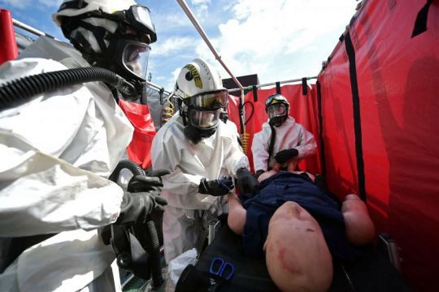 """ST reporter Cheryl Tee (second from left) helps to """"decontaminate a casualty"""" during a drill on board the Orca. The SCDF Marine Command is responsible for marine fire and rescue incidents and containment of chemical agents."""