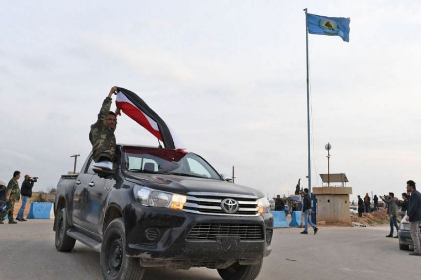 Pro-Syrian government forces wave Syrian national flags as they ride on pickup trucks upon arriving in Syria's northern region of Afrin on Feb 20, 2018.
