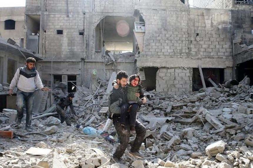 An injured boy being carried away from the rubble of damaged buildings in the rebel-held besieged town of Hamouriyeh, in Syria's eastern Ghouta district, yesterday.