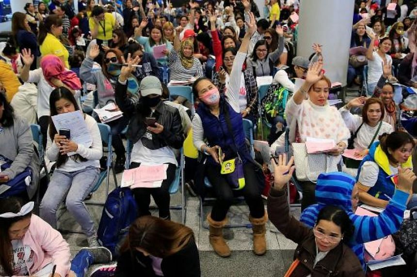 Filipinos working in Kuwait arriving at Ninoy Aquino International Airport in Manila yesterday, following President Rodrigo Duterte's call to evacuate workers after the body of a Filipino domestic maid was found stuffed inside a freezer in the Gulf s