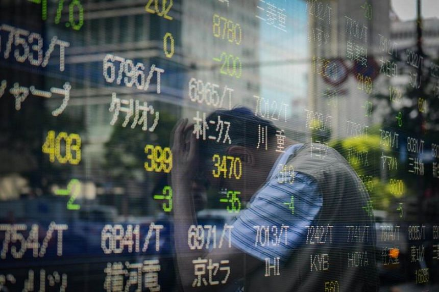 A pedestrian is reflected in an electronic stock board outside a securities firm in Tokyo, Japan.