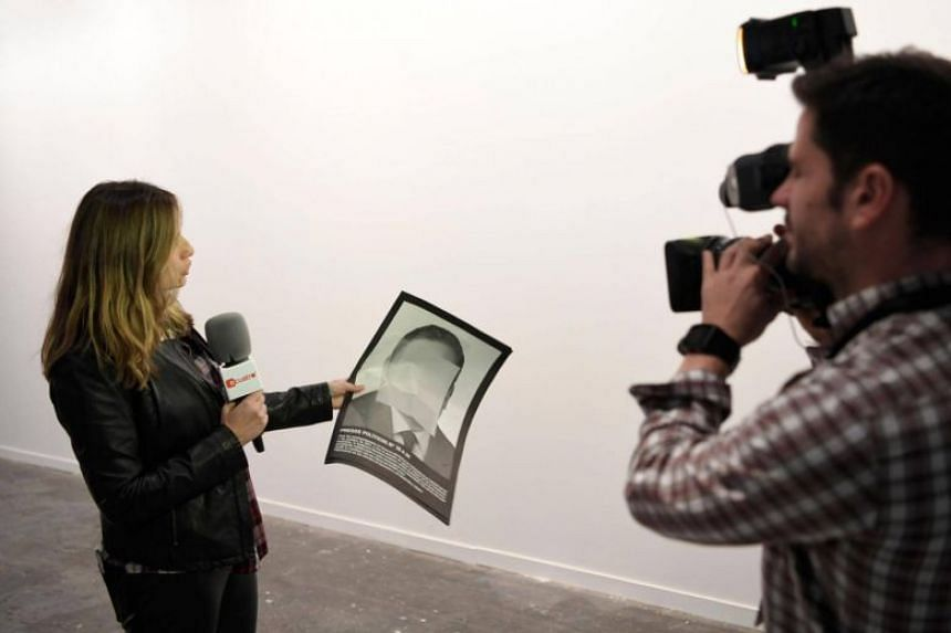 A journalist holds a photograph, part of the art-installation by Spanish artist Santiago Sierra 'Political prisoners of contemporary Spain' as she informs on its removal from ARCO art fair in Madrid, on Feb 21, 2018.